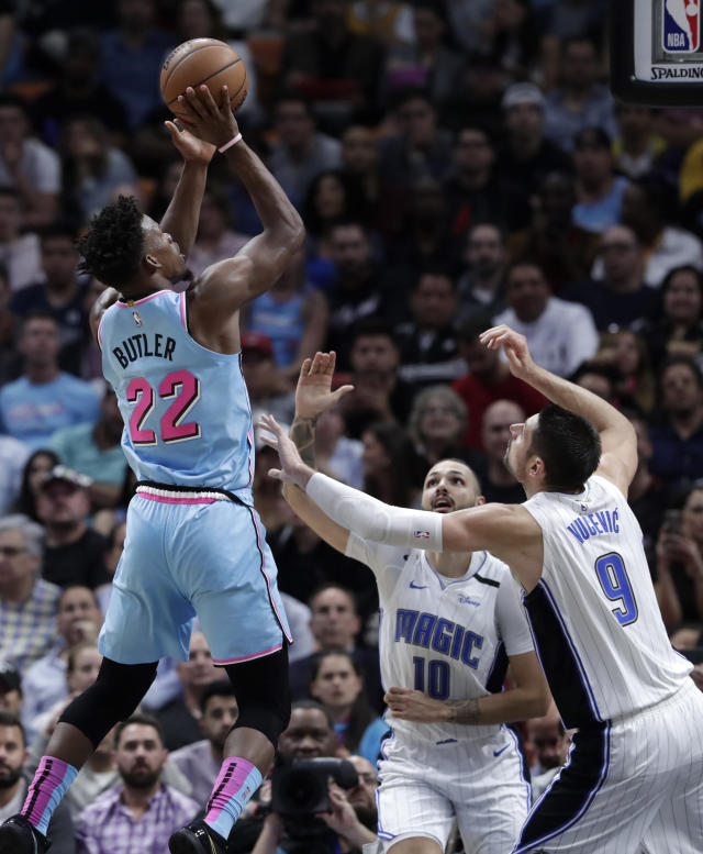 Miami Heat forward Jimmy Butler (22) shoots as Orlando Magic guard Evan Fournier (10) and center Nikola Vucevic (9) defend during the first half of an NBA basketball game, Monday, Jan. 27, 2020, in Miami. (AP Photo/Lynne Sladky)