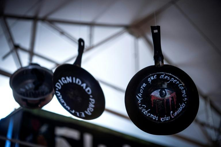 """Pots and pans used in Chile's months of anti-government demos, bearing the words: """"Now that we woke up, we must be conscious"""""""