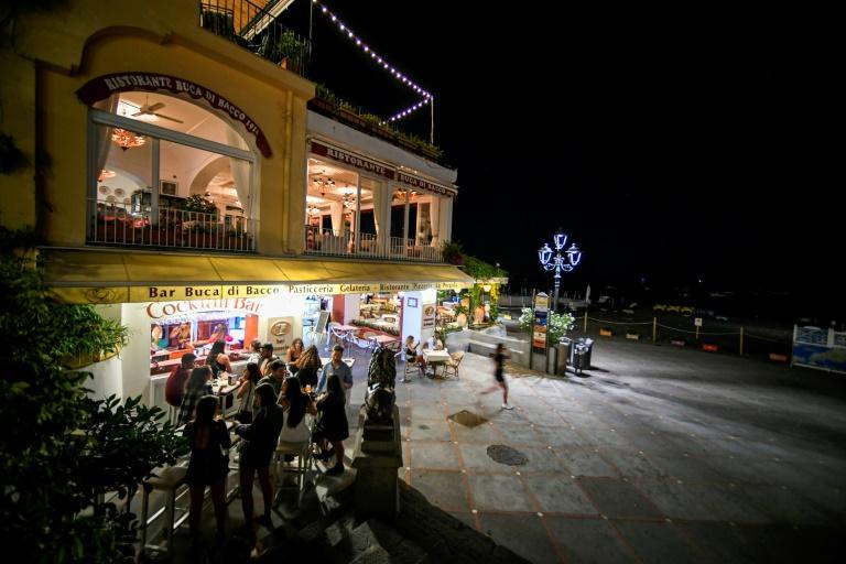 Tourists have a drink outside a bar by the sea in Positano in June