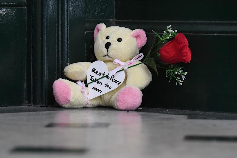 A tribute is seen outside the apartment where Michaela Dunn was found dead.