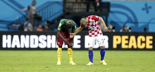 Croatia's Danijel Pranjic, right, shakes hands with Cameroon's Dany Nounkeu after the group A World Cup soccer match between Cameroon and Croatia at the Arena da Amazonia in Manaus, Brazil, Wednesday, June 18, 2014. Croatia won the match 4-0. (AP Photo/Dolores Ochoa)