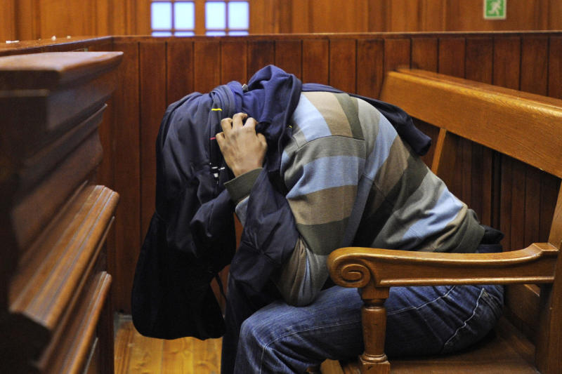 South African Mziwamadoda Qwabe covers his face with his jacket as he sits in the dock at court in Cape Town, South Africa, Wednesday, Aug. 8, 2012. Qwabe, one of two South African men accused of being hired by a British newlywed to kill his Swedish bride pleaded guilty to his involvement in the slaying, a prosecution spokesman said. Mziwamadoda Qwabe pleaded guilty to kidnapping, robbery, murder and illegal possession of a firearm over the November 2010 killing of Anni Dewani, whose body was found in an abandoned taxi in Cape Town's impoverished Gugulethu township, said Eric Ntabazalila, a spokesman for South Africa's National Prosecuting Authority. (AP Photo/Str) SOUTH AFRICA OUT