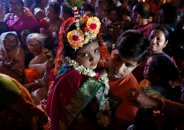 <p>Soumili Mukherjee, a five-year old girl dressed as a Kumari, who is worshipped as part of the Durga Puja rituals, is carried by her father to a temporary platform called pandal, during the Hindu religious festival Durga Puja in Kolkata, India, Sept. 28, 2017. (Photo: Rupak De Chowdhuri/Reuters) </p>