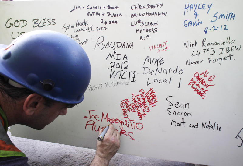 """FILE- In this Aug. 2, 2012 file photo, a construction worker signs a ceremonial steel beam at One World Trade Center in New York. The beam was signed by President Barack Obama with the notes: """"We remember,"""" ''We rebuild"""" and """"We come back stronger!"""" during a ceremony at the construction site June 14. The beam, having since adorned with the autographs of workers and police officers at the site, will be sealed into the structure of the tower, which is scheduled for completion in 2014. (AP Photo/Mark Lennihan, File)"""