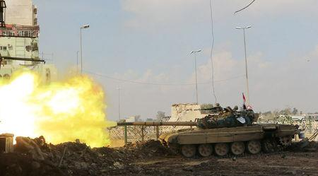 A tank of Iraqi rapid response forces fire against Islamic State militants at the Bab al-Tob area in Mosul