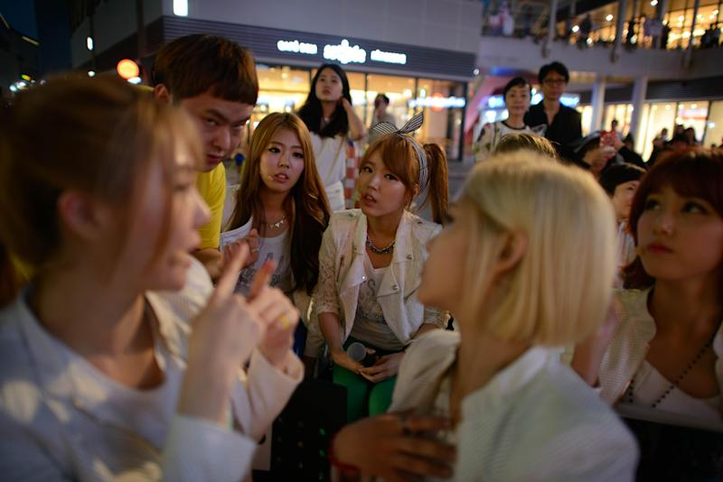 Manager Park In-Seo (2nd L) talks to K-pop group 'Billion' members Ki-Ryeon (L), Janet (centre L), Betty (centre R), Ray (2nd L), and Seul-gi (R) prior to a performance at a shopping mall in Ilsan, near Seoul, June 10, 2014 (AFP Photo/Ed Jones)