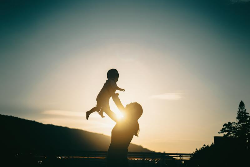 Silhouette of mother raising baby girl in the air outdoors against sky during a beautiful sunset (Photo: d3sign via Getty Images)