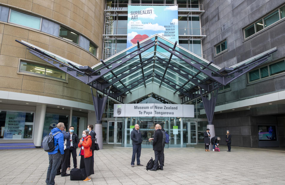 Visitors stand outside Te Papa museum in Wellington, New Zealand, Wednesday, June, 23, 2021. After enjoying nearly four months without any community transmission of the coronavirus, New Zealanders were on edge Wednesday after health authorities said an infectious traveler from Australia had visited over the weekend. (Mark Mitchell/NZ Herald via AP)