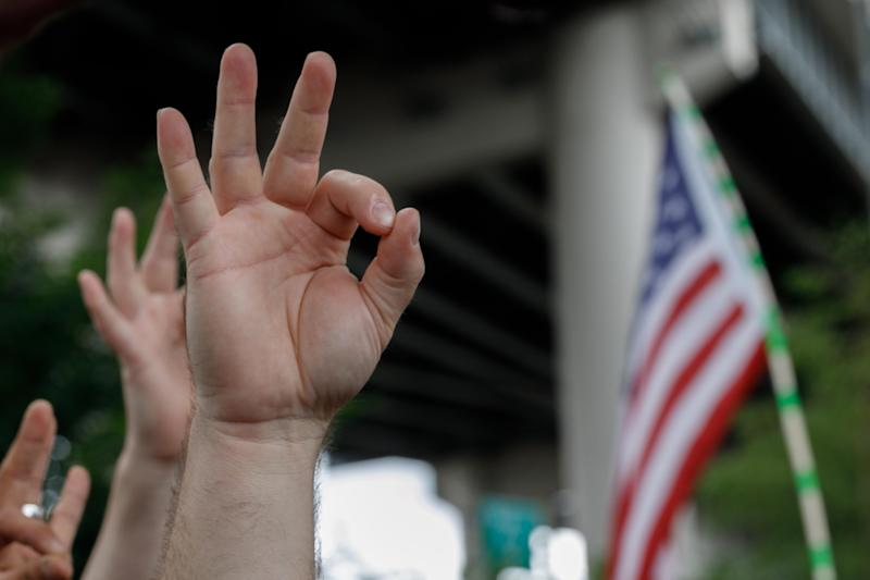 "A far-right demonstrator makes the OK hand gesture believed to have white supremacist connotations during ""The End Domestic Terrorism"" rally at Tom McCall Waterfront Park on August 17, 2019 in Portland, Oregon. - No major incidents were reported on Saturday afternoon in Portland (western USA) during a far-right rally and far-left counter-demonstration, raising fears of violent clashes between local authorities and US President Donald Trump, who was monitoring the event ""very closely"". (Photo by John Rudoff / AFP) (Photo credit should read JOHN RUDOFF/AFP/Getty Images)"