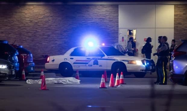 RCMP officers stand near a body covered with a tarp in the parking lot of a shopping complex in Burnaby, B.C., on May 13. Police later said the victim, Jaskeert Kalkat, was connected to gangs and targeted.