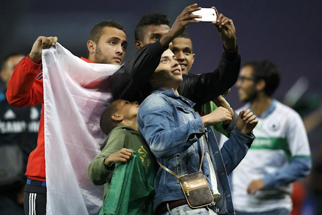 Algeria supporters take a photograph on the pitch after the international friendly soccer match between Algeria and Romania at the Stade de Geneve stadium, in Geneva, Switzerland, Wednesday June 4, 2014. World Cup-bound Algeria beat Romania 2-1 in a warm-up match on Wednesday marred by widespread fan disorder. The teams were taken off the field after 43 minutes and Algeria coach Vahid Halilhodzic appealed for fans to stop throwing lit flares and bottles. (AP Photo/Salvatore Di Nolfi, Keystone)