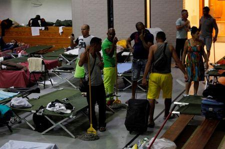 Cuban migrants clean inside Houchen Activities Center which is use as shelter to wait for help from relatives or friends, after arriving by plane from Panama to Mexico, as they make their way to the U.S in El Paso