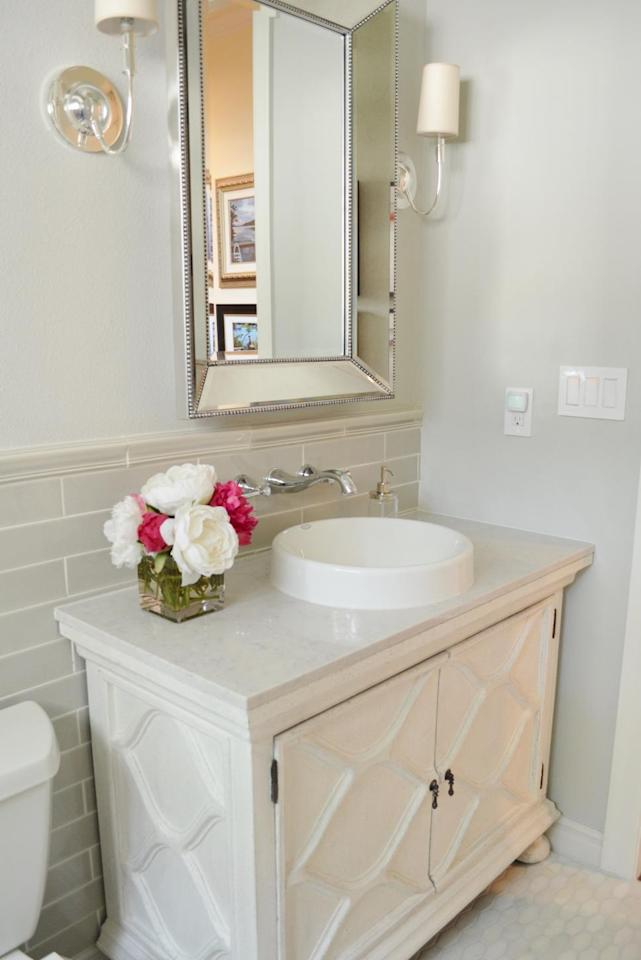"<p>Soft gray walls, marble flooring and a furniture-style vanity create an elegant spot for guests to freshen up. <a href=""http://people.hgtv.com/professionals/heather-scott-home---design?oc=PTNR-YahooRealEstate-HGTV-bath_remodels_5000"">Heather Scott Home & Design</a> removes the wall-mounted cabinet above the toilet, making the space feel much larger and brighter.</p>"