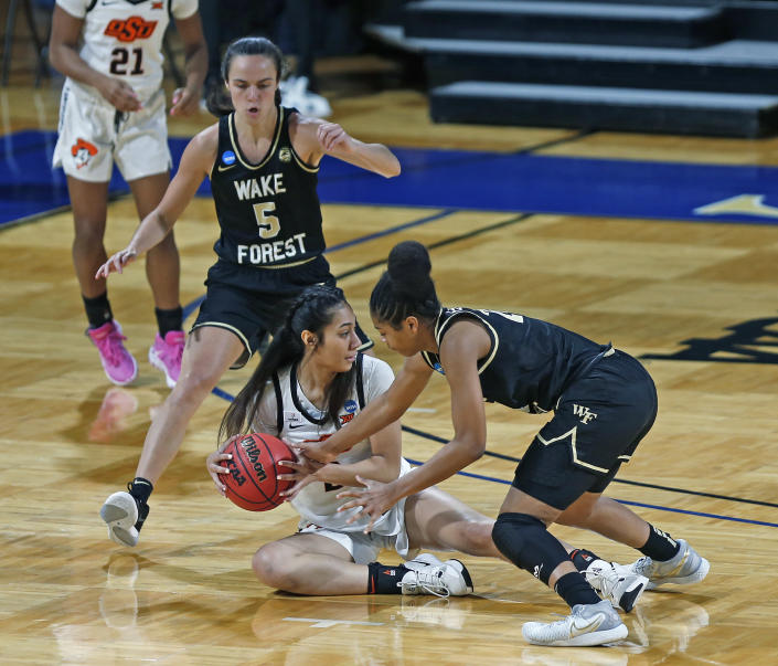 Oklahoma State guard Neferatali Notoa (2) struggles with Wake Forest forward Christina Mora for a loose ball during the first half of a college basketball game in the first round of the women's NCAA tournament at the Greehey Arena in San Antonio, Texas, Sunday, March 21, 2021. (AP Photo/Ronald Cortes)