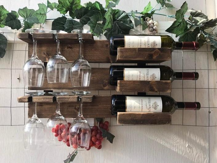 """This custom-made mounted wine rack is another nice way to store Dad's preferred wine glasses along with his favorite bottles of Cabernet, Malbec, and Chardonnay. $58, Etsy. <a href=""""https://www.etsy.com/listing/790632531/free-shipdistressed-wooden-wall-mounted"""" rel=""""nofollow noopener"""" target=""""_blank"""" data-ylk=""""slk:Get it now!"""" class=""""link rapid-noclick-resp"""">Get it now!</a>"""