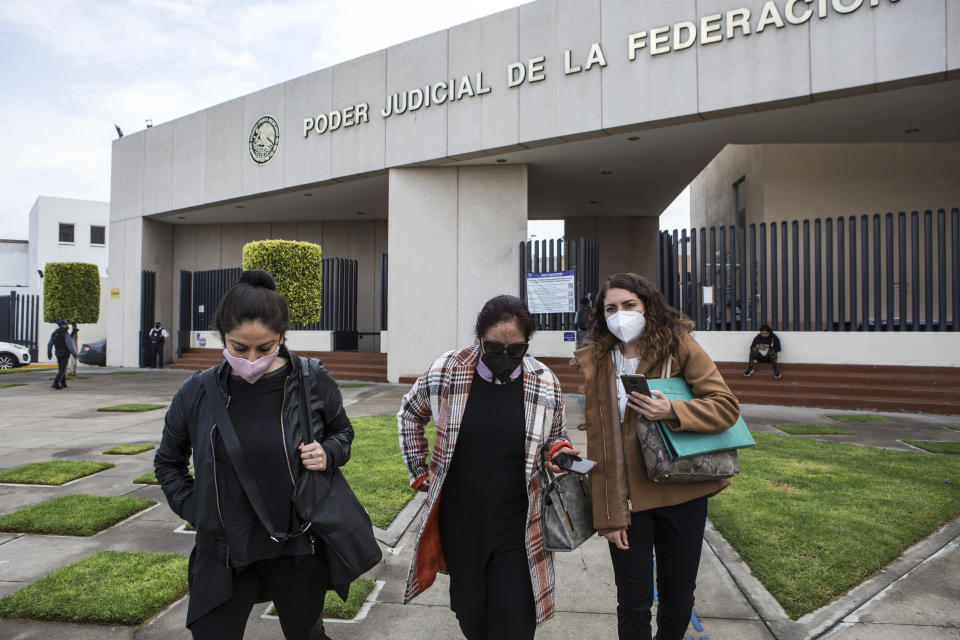 Carmen Sánchez, who survived an acid attack by her ex-partner seven years ago when she was 30, walks between her psychologist Jazmín Ramírez, left, and lawyer Jimena Saavedra, as they leave the Federal Judicial Branch building in Ciudad Nezahualcóyotl, State of Mexico, Mexico, Friday, July 22, 2021, after the court cancelled a hearing with Carmen's attacker amid an ongoing investigation into classifying her attack as an attempted femicide. Sanchez started a foundation that bears her name, seeking justice in her case, talking with other survivors, seeking out donors, psychologists and doctors. (AP Photo/Ginnette Riquelme)