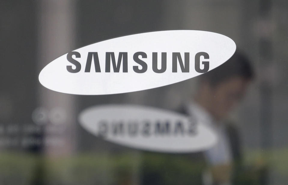 FILE - In this April 30, 2019, file photo, an employee walks past a logo of the Samsung Electronics Co. at its office in Seoul, South Korea. Pressure is mounting on South Korean President Moon Jae-in to pardon Samsung heir Lee Jae-yong, who is back in prison after his conviction in a massive corruption scandal, even though business has rarely looked better at South Korea's largest company. (AP Photo/Ahn Young-joon, File)