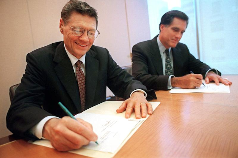 "FILE - In this Sept. 25, 1998 file photo, provided by Domino's Pizza, Thomas Monaghan, founder and chairman of Domino's Pizza, Inc., left, and Mitt Romney, managing director of Bain Capital, Inc., sign an agreement for Monaghan to sell a ""significant portion"" of his stake in the company to Bain Capital, in New York. A businessman at his core, Mitt Romney was legendary in the private sector for his reliance on reams of information and extensive research to decide which companies to take over. And, when interviewing potential employees, he favored question-and-answer sessions designed to make recruits think on their feet and provide clues about how they approached situations.  (AP Photo/Domino's Pizza, Scott Gries, File)"