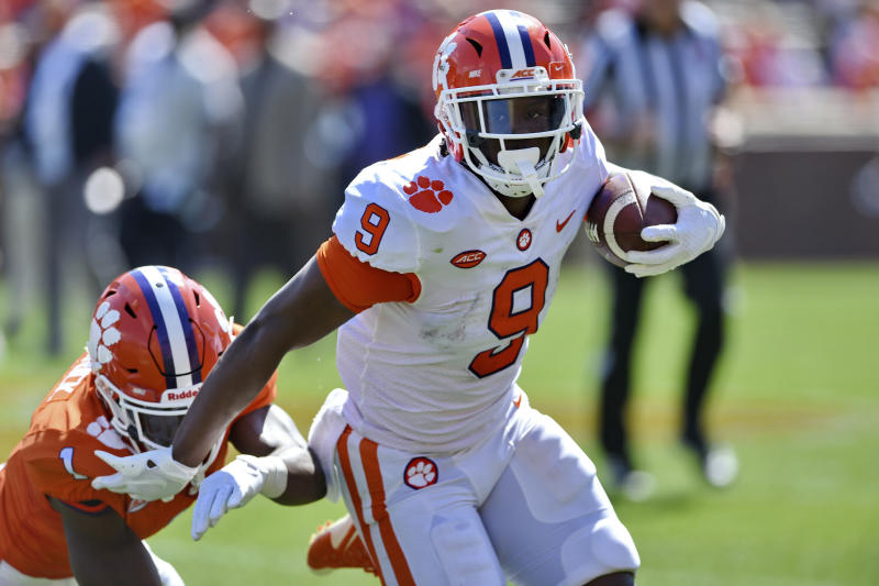 FILE - In this April 6, 2019, file photo, Clemson's Travis Etienne (9) rushes out of the tackle attempt by Derion Kendrick during Clemson's annual Orange and White NCAA college football spring scrimmage in Clemson, S.C. Etienne is one of three Clemson Tigers selected an AP preseason All-American along with quarterback Trevor Lawrence and linebacker Isaiah Simmons. (AP Photo/Richard Shiro, File)