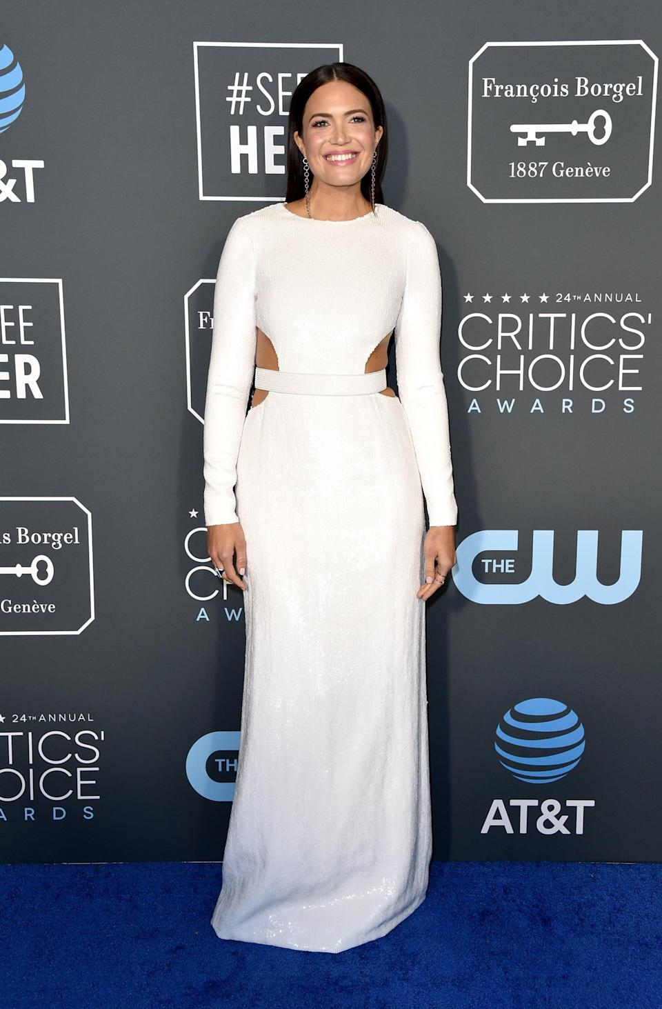 """<p><a rel=""""nofollow noopener"""" href=""""https://www.popsugar.co.uk/Mandy-Moore"""" target=""""_blank"""" data-ylk=""""slk:Mandy Moore"""" class=""""link rapid-noclick-resp"""">Mandy Moore</a> wearing a white cutout dress by Michael Kors Collection with Katkim jewels and Jimmy Choo heels.</p>"""