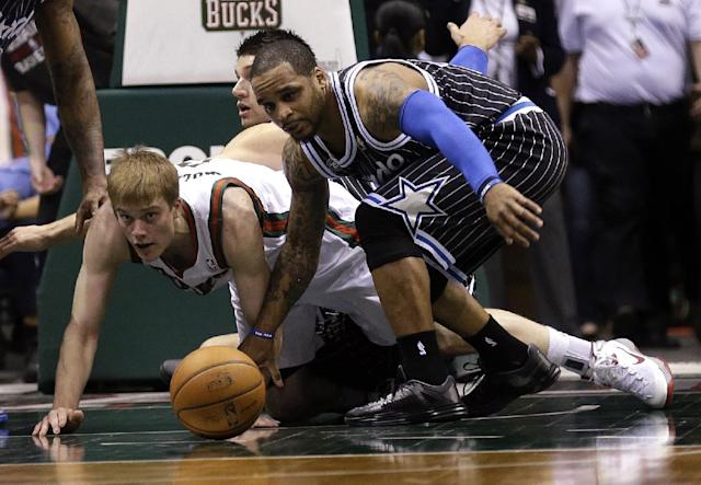 Orlando Magic's Jameer Nelson, right, and Milwaukee Bucks' Nate Wolters reach for the loose ball during the first half of an NBA basketball game, Monday, March 10, 2014, in Milwaukee. (AP Photo/Jeffrey Phelps)