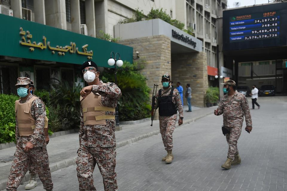 Paramilitary officers inspect the premisses of the Pakistan Stock Exchange building following an attack by gunmen in Karachi on June 29, 2020. - At least six people were killed when gunmen attacked the Pakistan Stock Exchange in Karachi on June 29, with a policeman among the dead after the assailants opened fire and hurled a grenade at the trading floor, police said. (Photo by Rizwan TABASSUM / AFP) (Photo by RIZWAN TABASSUM/AFP via Getty Images)