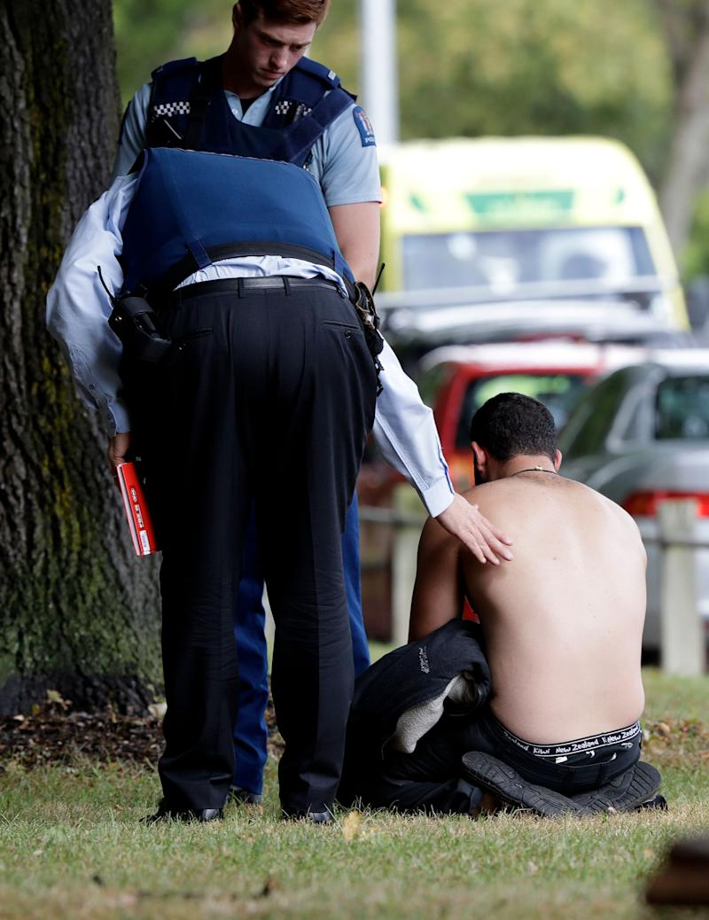 Police console a man outside a mosque in central Christchurch after a mass shooting in New Zealand on March 15, 2019.