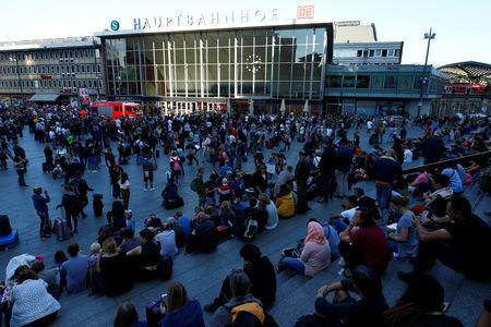 Passengers wait outside the main train station in Cologne, Germany, October 15, 2018, after the train station was closed after hostage-taking.     REUTERS/Thilo Schmuelgen