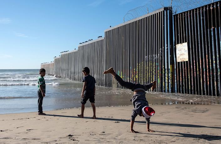 Children traveling with the Central American migrants that hope to reach the United States, play at the beach next to the US-Mexico border fence in Playas de Tijuana, Baja California State, Mexico, on Dec. 29, 2018.  El Salvador insisted Saturday that it is taking steps to curb illegal migration to the United States, fending off criticism from President Donald Trump, a day after he threatened to cut off aid to nations in Central America's Northern Triangle, Honduras, Guatemala and El Salvador.