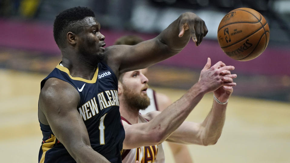 New Orleans Pelicans' Zion Williamson, left, and Cleveland Cavaliers' Dean Wade battle for a rebound in the second half of an NBA basketball game, Sunday, April 11, 2021, in Cleveland. (AP Photo/Tony Dejak)