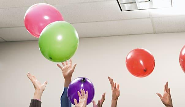 Office workers playing with balloons