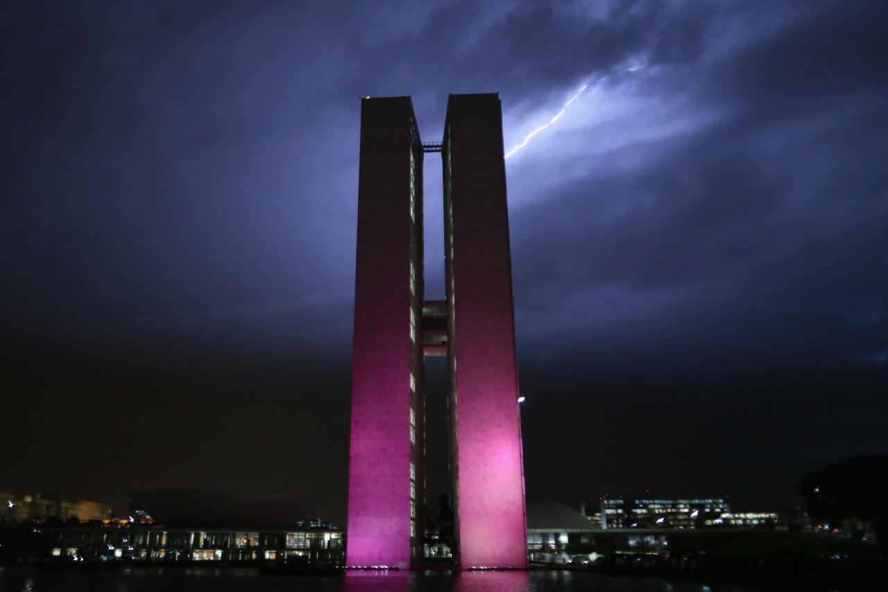 Brazil's National Congress headquarters is illuminated with pink lights as lightning is seen in Brasilia October 8, 2013. The main buildings of Brasilia are illuminated in pink as part of 'Pink October', a campaign that recognises and celebrates October as International Breast Cancer Awareness Month. REUTERS/Ueslei Marcelino (BRAZIL - Tags: POLITICS HEALTH TPX IMAGES OF THE DAY ENVIRONMENT)