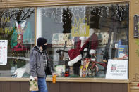 Christmas cards and costumes are displayed in the window at Mid Central Printing & Mailing store in Wilmette, Ill., Friday, Dec. 18, 2020. Isolated by the coronavirus pandemic, Americans are sending more Christmas and holiday cards to stay in touch this year. (AP Photo/Nam Y. Huh)