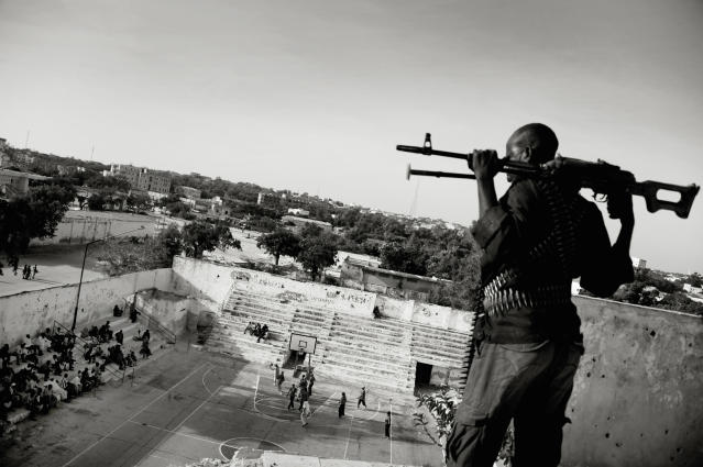 """In this photo provided on Friday Feb. 15, 2013 by World Press Photo, the 1st prize Sports – Sports Features Stories by Jan Grarup, Denmark, for Laif, shows the Somali basketball association pays armed guards to watch over and protect Suweys and her team when they play. In Mogadishu, the war-torn capital of Somalia, young women risk their lives to play basketball. Suweys, the 19-year-old captain of a women's basketball team, and her friends defy radical Islamist views on women's rights. They have received many death threats from not only al-Shabaab militias and radical Islamists, but some male members of their own families. """"I just want to dunk,"""" said Suweys. It is on the basketball court she feels happiest. """"Basketball makes me forget all my problems,"""" Mogadishu, Somalia, Feb. 21, 2012. (AP Photo/Jan Grarup, Laif)"""