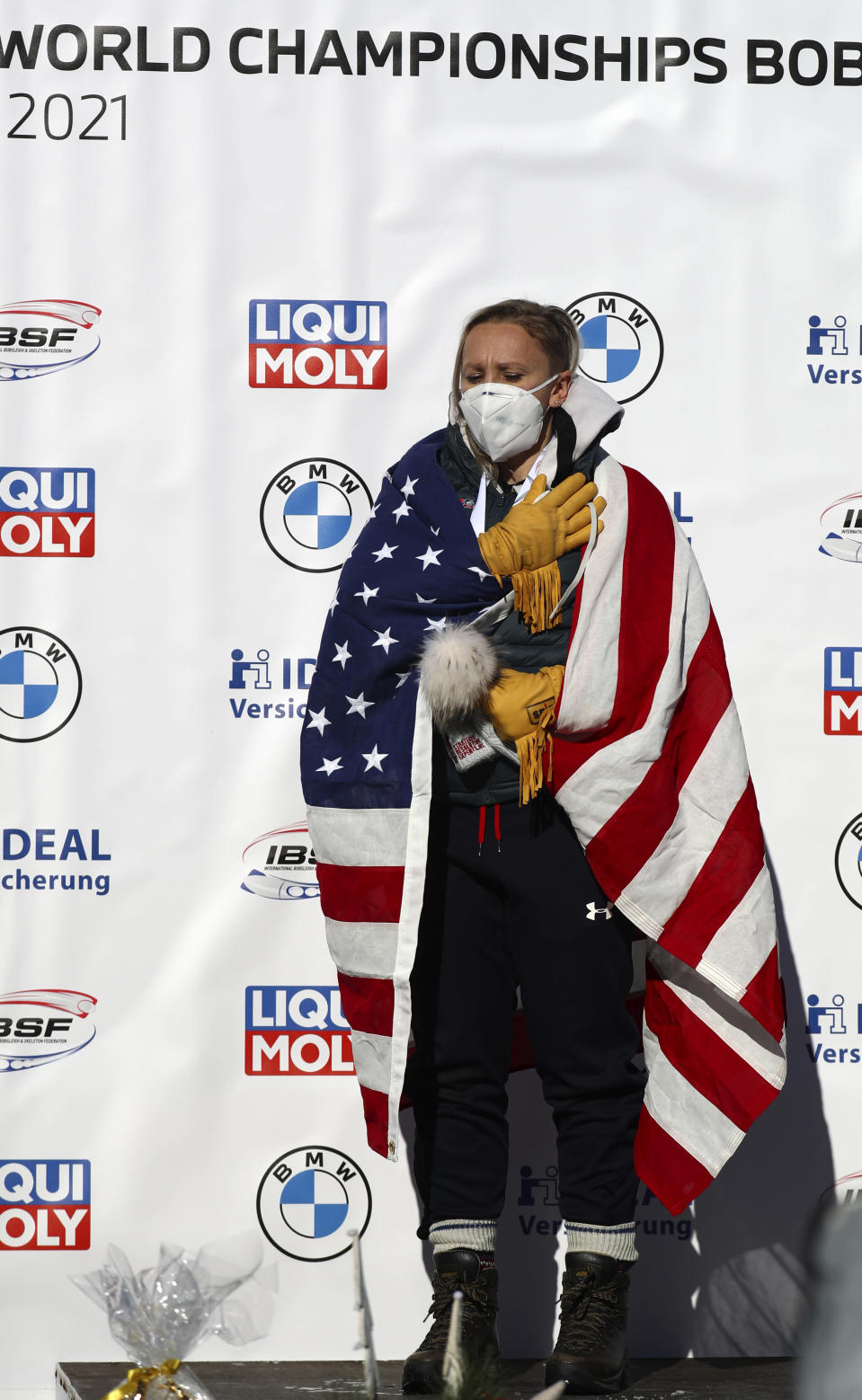 Bobsleigh pilot Kaillie Humphries of the United States stands on the podium after taking first place in the women's monobob race at the Bobsleigh and Skeleton World Championships in Altenberg, Germany, Sunday, Feb.14, 2021. (AP Photo/Matthias Schrader)