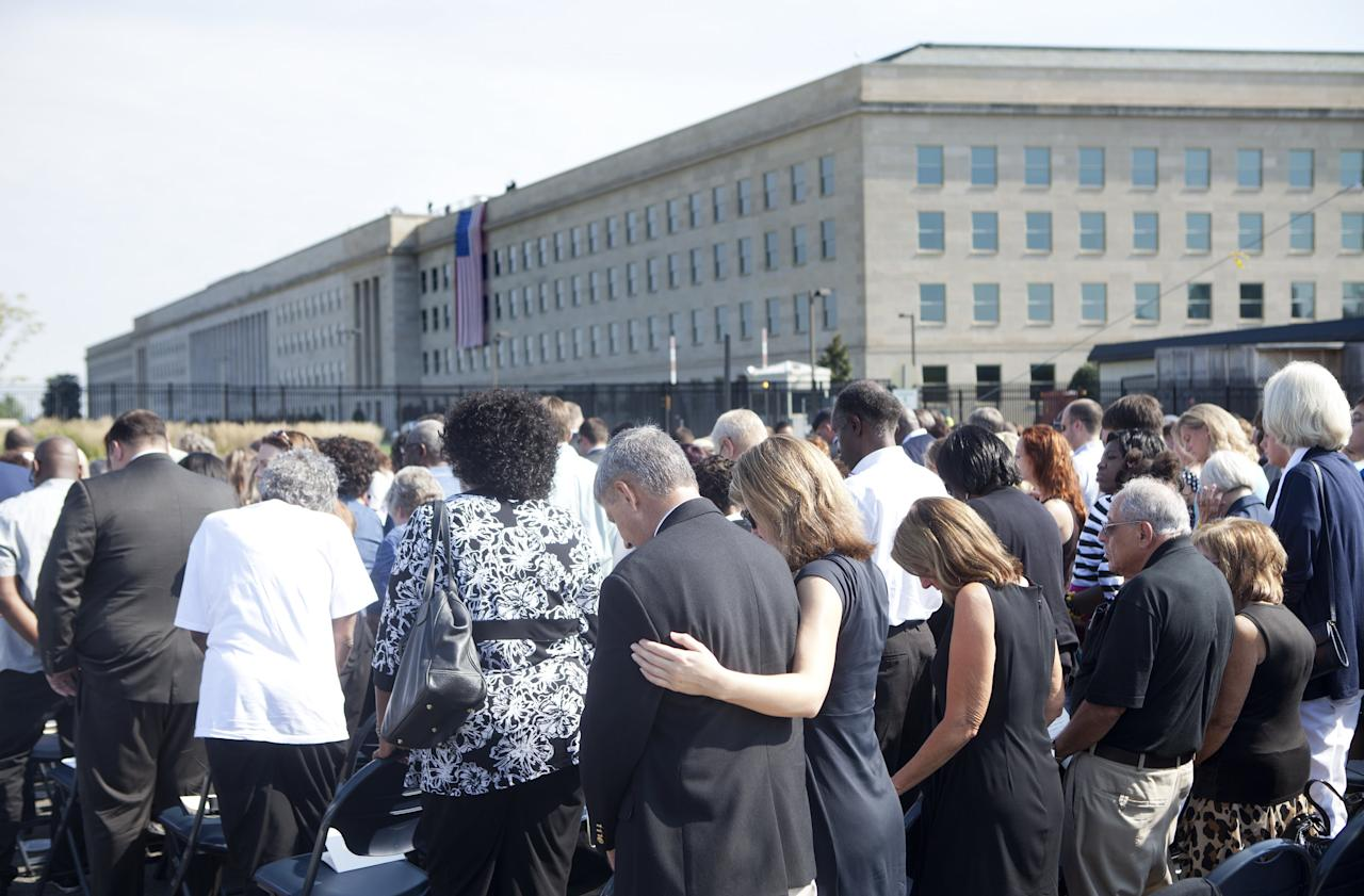 ARLINGTON, VA - SEPTEMBER 11:  People bow their heads in prayer during a memorial service at the Pentagon September 11, 2011 in Arlington, Virginia.  Vice President Joseph R. Biden, Secretary of Defense Leon E. Panetta, Chairman of the Joint Chief of Staff Navy Admiral Mike Mullen and others will attend a memorial service at the Pentagon Memorial to commemorate the 10th anniversary the September 11, 2001 terrorist attacks on the United States.  (Photo by Brendan Smialowski/Getty Images)