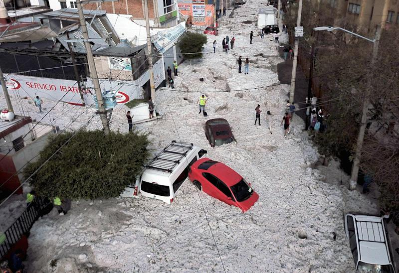 Vehicles buried in hail are seen in the streets in the eastern area of Guadalajara, Jalisco state, Mexico, on June 30, 2019.