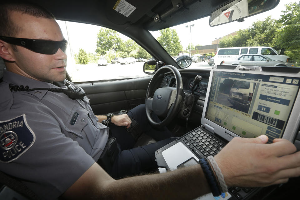 FILE- In this July 16, 2013, file photo, Officer Dennis Vafier, of the Alexandria Police Department, uses a laptop in his squad car to scan vehicle license plates during his patrols in Alexandria, Va. It would violate people's privacy to publicly release raw data collected by automated license plate readers that police use to determine whether vehicles are linked to crime, but there may be ways to make the information anonymous that would require it to be disclosed, the California Supreme Court said Thursday, Aug. 31, 2017. (AP Photo/Pablo Martinez Monsivais, File)