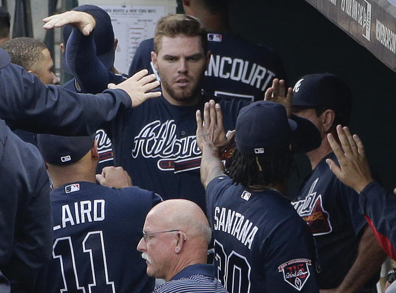 Atlanta Braves' Freddie Freeman (5) is greeted by teammates in the dugout after scoring against the New York Mets in the first inning of a baseball game, Thursday, July 10, 2014, in New York. (AP Photo/Julie Jacobson)