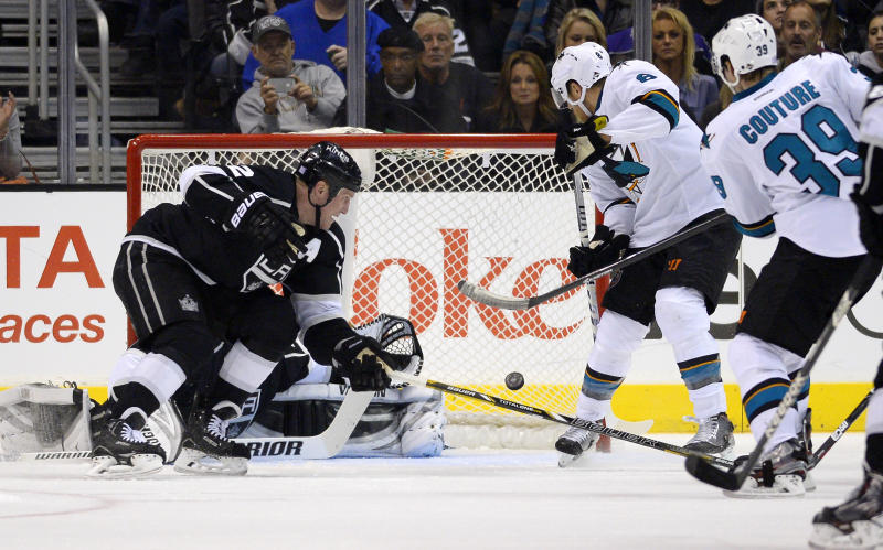 San Jose Sharks center Logan Couture, right, scores on Los Angeles Kings goalie Jonathan Quick, second from left, as defenseman Matt Greene, left, defends and center Joe Pavelski, second from right, looks on during the second period of their NHL hockey game on Wednesday, Oct. 30, 2013, in Los Angeles. (AP Photo/Mark J. Terrill)