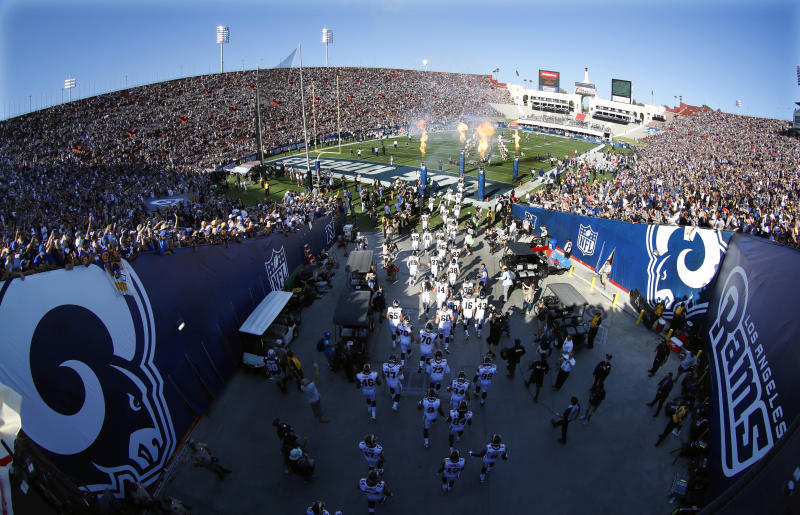 FILE - In this Aug. 13, 2016, file photo, the Los Angeles Rams take the field at Los Angeles Memorial Coliseum for a preseason NFL football game against the Dallas Cowboys, in Los Angeles. Opened in 1923, the Coliseum first gained the Rams as a tenant in 1946 when they moved west from Cleveland. (AP Photo/Ryan Kang, File)