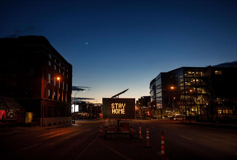 A sign telling people how to prevent COVID-19 by staying home, sits in the empty downtown, in Edmonton on March 26, 2020. (Photo: Jason Franson/CP)