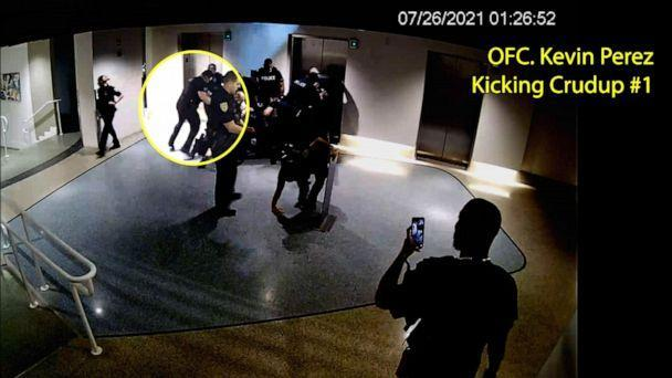 PHOTO: Officer Kevin Perez is seen as he motions to kick Dalonta Crudup while Khalid Vaughn stands on the far right recording video with his phone, in an image taken from hotel surveillance video released by the Miami-Dade State Attorney's Office. (Miami-Dade State Attorney's Office)