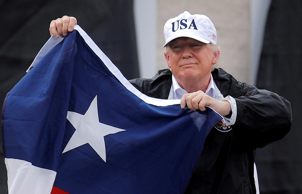 <p>President Donald Trump holds a flag of the state of Texas after receiving a briefing on Tropical Storm Harvey relief efforts at a local fire station where residents gathered to welcome the president in Corpus Christi, Texas, Aug. 29, 2017. (Photo: Carlos Barria/Reuters) </p>