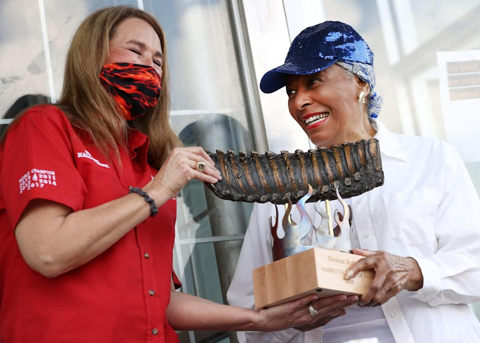 Cozy Corner Matriarch Desiree Robinson is officially inducted into the The American Royal Barbecue Hall of Fame, receiving her trophy for the award from the first female to ever win the title, Memphis Barbecue Co.'s Melissa Cookston.