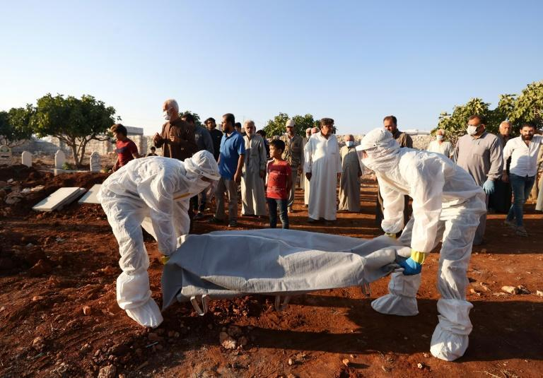 Paramedics transport the corpse of a Syrian who died of the coronavirus, during a funeral on September 30, 2021 in Barisha village, Idlib province, where the number of cases has increased sharply (AFP/OMAR HAJ KADOUR)