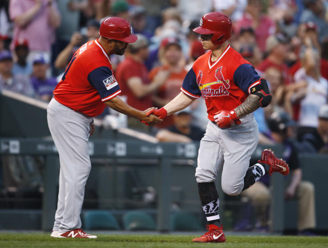 St. Louis Cardinals third base coach Jose Oquendo, left, congratulates Tyler O'Neill who circles the bases after hitting a solo home run off Colorado Rockies starting pitcher Antonio Senzatela in the second inning of a baseball game Friday, Aug. 24, 2018, in Denver. (AP Photo/David Zalubowski)