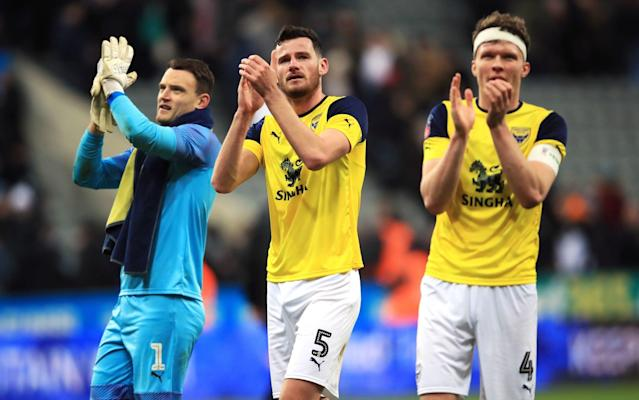 Oxford United players celebrate their 0-0 draw at St James' Park over a side two divisions ahead of them - PA