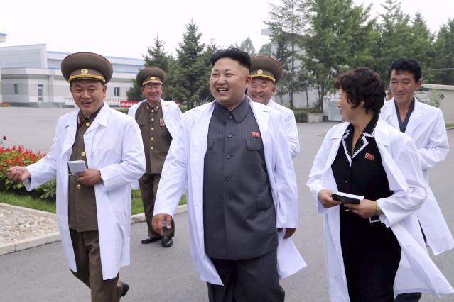 North Korean leader Kim Jong Un (front C) smiles as he gives field guidance during a visit to the November 2 Factory of the Korean People's Army (KPA) in this undated photo released by North Korea's Korean Central News Agency (KCNA) in Pyongyang August 24, 2014. REUTERS/KCNA (NORTH KOREA - Tags: POLITICS MILITARY) ATTENTION EDITORS - THIS PICTURE WAS PROVIDED BY A THIRD PARTY. REUTERS IS UNABLE TO INDEPENDENTLY VERIFY THE AUTHENTICITY, CONTENT, LOCATION OR DATE OF THIS IMAGE. FOR EDITORIAL USE ONLY. NOT FOR SALE FOR MARKETING OR ADVERTISING CAMPAIGNS. THIS PICTURE IS DISTRIBUTED EXACTLY AS RECEIVED BY REUTERS, AS A SERVICE TO CLIENTS. NO THIRD PARTY SALES. NOT FOR USE BY REUTERS THIRD PARTY DISTRIBUTORS. SOUTH KOREA OUT. NO COMMERCIAL OR EDITORIAL SALES IN SOUTH KOREA