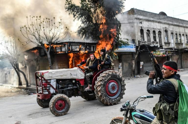 A Turkish-backed Syrian rebel drives past a burning shop in the city of Afrin in northern Syria on March 18, 2018